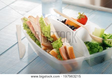 Full lunch box of healthy food on wooden table close up. Healthy lunch concept