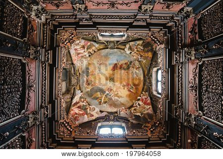 June 14th, 2017 - Milan, Lombardy, Italy. Interior of side chapel in San Bernardino alle Ossa church. Ossuary decorated with human skulls and bones and Triumph of Souls and Flying Angels fresco.