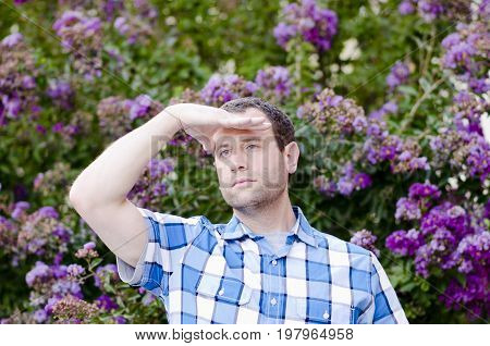 Optimistic man in a plaid shirt looking out hopeful for the future with a bush with purple flowers in the background.