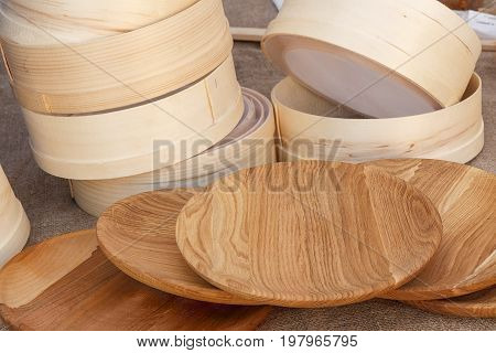 Wooden plate and the sieve by hand on the fair lie on coarse linen. Wooden plates have a beautiful texture. Various wooden utensils in retro style. The dishes sold at the fair.