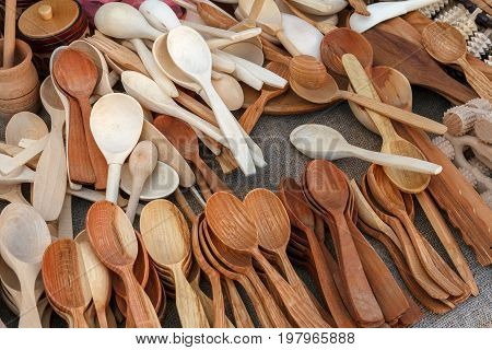 Wooden spoons are handmade at the fair, prepared for sale. Wooden spoons lie on a flat surface. Various wooden utensils in retro style. The devices are sold at the fair.