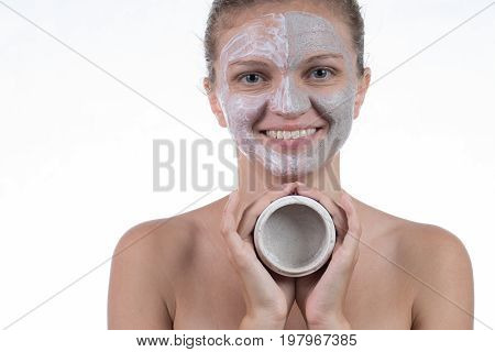 Two cosmetic mask of gray clay with scrub and cream on the face of a beautiful young girl and a jar with clay