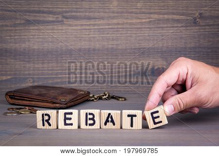Rebate. Wooden letters on dark background. Office desk