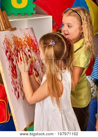 Children painting finger on easel. Group of kids girl learn paint in class school. Kindergarten interior on background. Picture with prints of children's hands. They rest in a children's club.