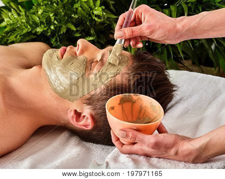 Mud facial mask of man in spa salon. Massage with clay full face. Girl on with therapy room. Man lying wooden spa bed. Green leaves in the background.