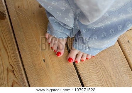 Legs with red pedicure in pajamas, top view. Female feet with a pedicure in red