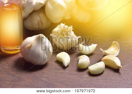 fresh garlic and oil in glass bottle on wooden background