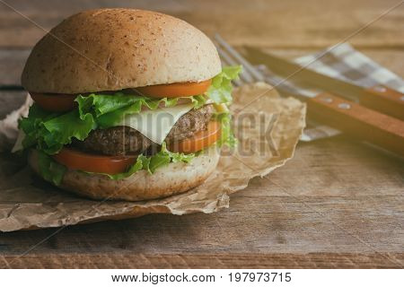 Homemade hamburger or sandwich on brown paper. Delicious sandwich hamburger with meat or pork ham cheese and fresh vegetable. Hamburger or sandwich is the popular fast food for brunch or lunch. Cheeseburger ready to served on wood table.