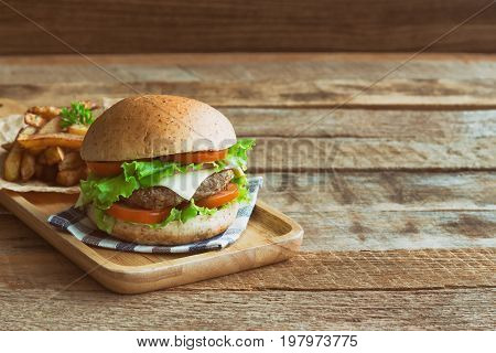 Homemade hamburger on plaid napkin with french fries. Delicious sandwich hamburger with meat or pork ham cheese and fresh vegetable. Hamburger or sandwich is the popular fast food for brunch or lunch. Cheeseburger ready to served.