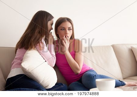 Two close girlfriends sharing scandalous news. Young attractive woman telling incredible secret to her friends ear while sitting on sofa in living room. Surprised lady listening interesting gossips