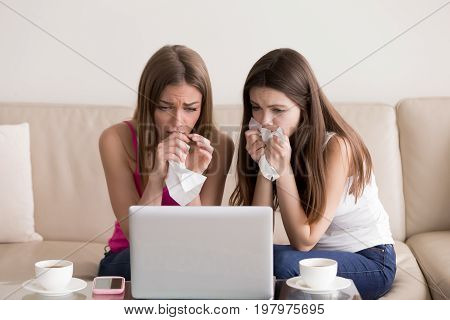 Two sentimental women friends upset crying and wiping tears with handkerchiefs while watching dramatic, sad movie, TV reality show or touching old home video on laptop while sitting on sofa at home