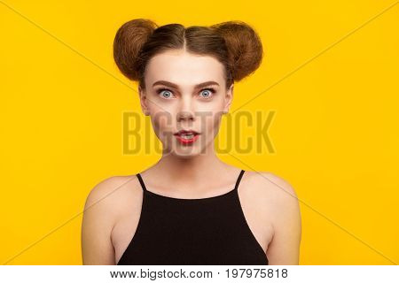 Brunette young woman shocked wearing black top staring at camera with open mouth standing against yellow background.