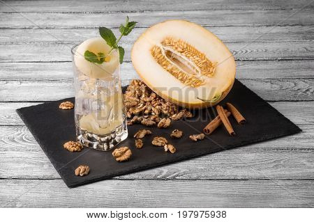 A composition of a cut melon, glass full of ice, mint leaves and melon honeydew, spicy cinnamon sticks and nutritious walnuts. Natural, healthful and tasteful ingredients on a gray wooden background.