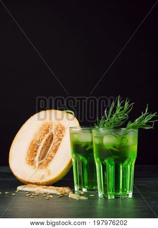 Two beautiful glasses of alcoholic drink with ice and tarragon leaves and delicious cut melon on a black background. Refreshing and fruity alcoholic summer beverages. Fresh melon and cold cocktails.