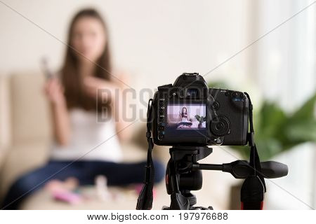Close up photo of digital camera on tripod with young woman using cosmetics image on LCD back screen and blurred scene on background. Female video blogger records vlog, beauty vloger streaming online