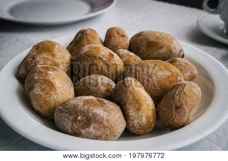 Papas arrugadas - small canarian wrinkly potatoes with salt on a plate close up. Brewed in sea water
