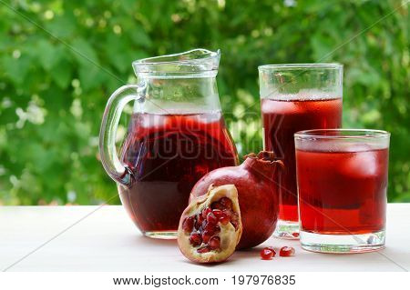 A jar and two glasses of pomegranate juice with ice and pomegranate.