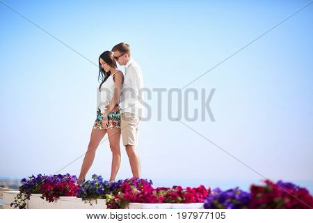 A fantastic couple on a bright blue sky background. Happy girlfriend and boyfriend hugging near pink and purple flowers. Lovers on a sea beach. Tourism and luxurious lifestyle concept. Copy space.