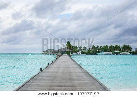 View of tropical resort from wooden pontoon on summer day