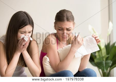 Two funny young women crying, wiping tears, blowing noses with handkerchiefs while sitting at home. Female friends suffering together because of heavy loss, cant calm down after emotional movie scene