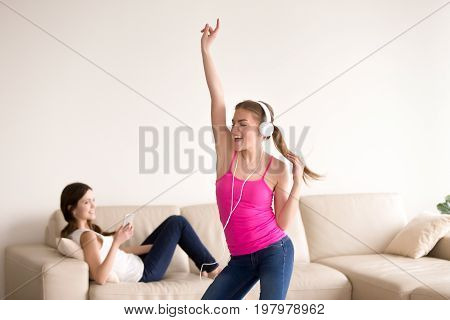 Attractive young happy lady dancing while listening her favorite song in headphones, smiling girlfriend lying in sofa nearby and using cellphone. Female friends entertain using modern digital gadgets