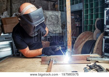 A bald strong man in a black welding mask is brewing a metal welding machine in a dark old garage working with a welding machine around a lot of tools for work