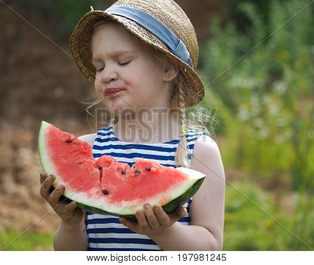 Funny little kid with a big watermelon. Funny face great emotion.
