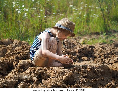 Little girl sculpts out of clay. A lot of dirt funny baby