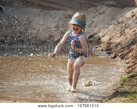 Incredibly happy child running fast on the water. Sand pit muddy water in a puddle much of the spill