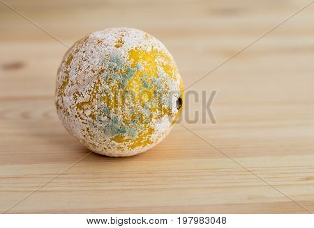 Lemon covered with mildew on a light wooden background. Copy space