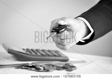 Businessman hand giving a car key car rental & pawn concepts - black & white tone