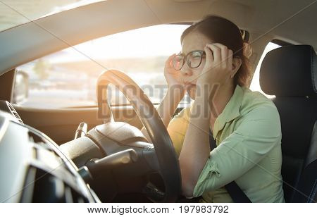 Asian glasses business woman having headache from migraine while driving a car with bad traffic jam on rush hours. Illness exhausted disease tired for overtime working concept.