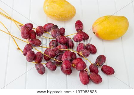 Two Raw Ripe Mango And Bunch Fresh Dates Branches White Wooden Background Top View