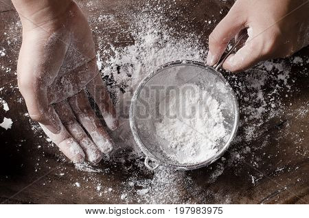 Hand sifting wheat flour for bakery cooking