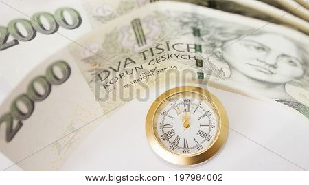 Czech banknotes like background and watch that have five to twelve time. Highest time for action.
