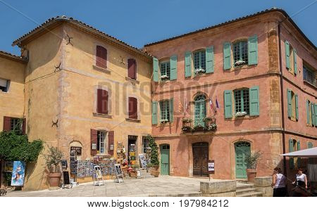 Small Square With Red Houses And Gift Shops At Village Of Roussillon, Provence, France