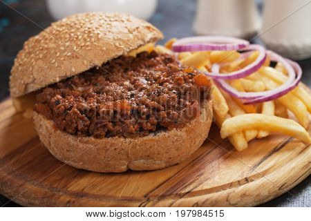 Ground beef burger sandwich with french fries served on wooden board