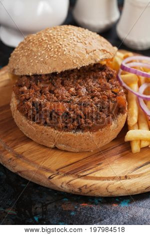 Ground beef burger sandwich with french fries on wooden board
