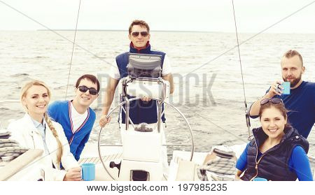 Group of friends traveling on a yacht, enjoying a good summer day and drinking a tea. Vacation, holiday and summertime concept.
