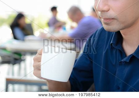 A man holding coffee cup about to drink - soft focus