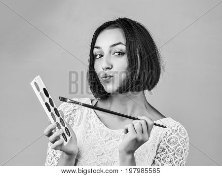 woman or girl with short hair in tracery blouse with paint and long paintbrush smiling black and white