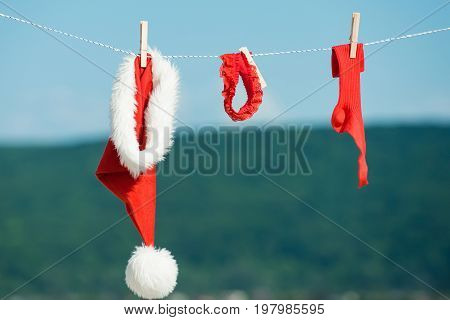 New year costume on blue sky. santa clothes for drying. Xmas red costume on rope with pin. Laundry and dry cleaning. Christmas clothes outdoor.