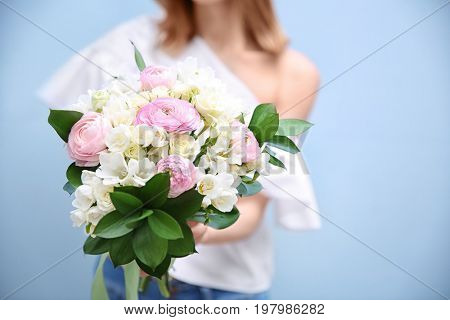 Young woman holding beautiful bouquet with white freesia on light background