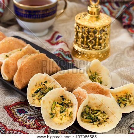 Traditional Arabic kataif pancakes stuffed cream and pistachios Prepared for iftar in Ramadan oud in gold on paisley background Square image