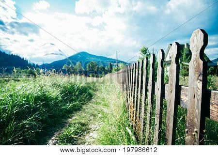 panoramic view of the old path with fence and mountains on background