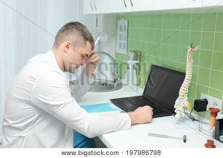 Young orthopedist working in office