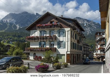 Cortina d'Ampezzo, Italy - September 24, 2011:  Autumnal corso Italia, the residential district in the town Cortina d'Ampezzo with mountain, Dolomites, Alps, Veneto, Italy, Europe. Visit in the place.