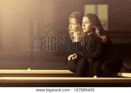 Two happy fashion teen girls sitting in sandbox on the playground. Stylish female models in black jeans and pullover outdoor