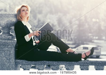 Happy young fashion business woman with a folder sitting on banister. Stylish female model in black suit outdoor