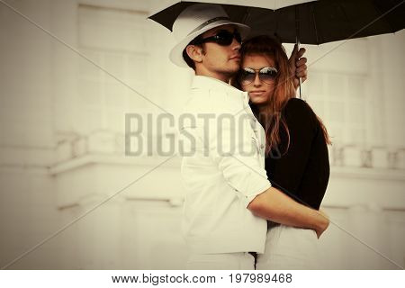 Young fashion couple in love with umbrella in city street. Stylish trendy male and female models in sunglasses outdoor